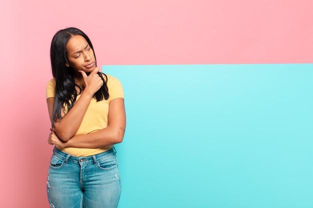 Jeune femme noire pensant, se sentant dubitative et confuse, avec différentes options, se demandant quelle décision prendre. concept d'espace de copie