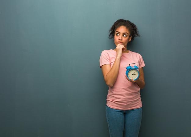 Jeune femme noire pense à une idée. elle tient un réveil.