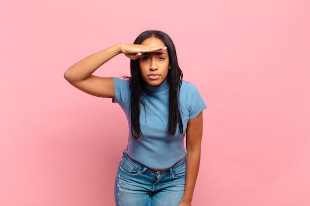 Jeune femme noire à la perplexité et étonné, avec la main sur le front à la recherche de loin, regarder ou chercher