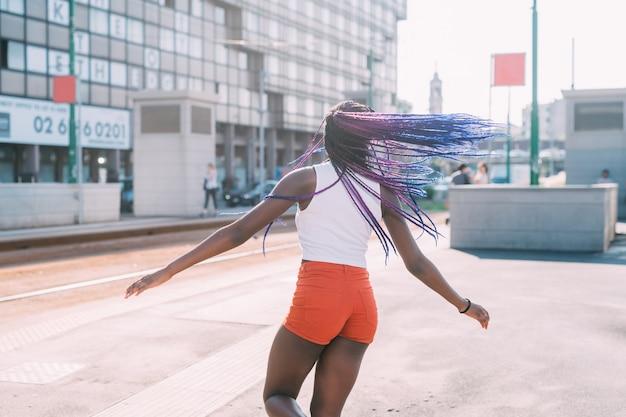 Jeune femme noire en plein air répand les bras se sentir libre