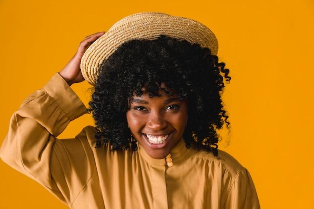 Jeune femme noire à pleines dents souriante et tenant un chapeau de paille