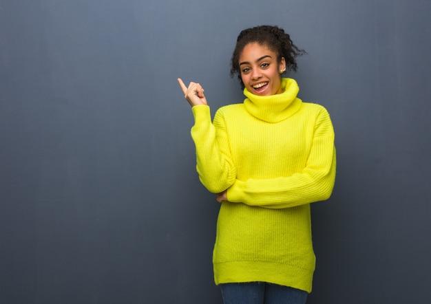 Jeune femme noire pointant sur le côté avec le doigt