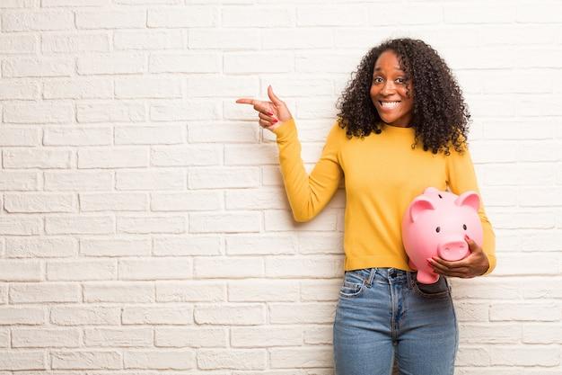 Jeune femme noire pointant sur le côté, souriant, présentant quelque chose