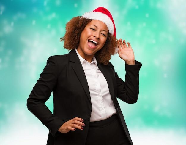 Jeune femme noire portant un bonnet de noel chirstmas dansant et s'amusant