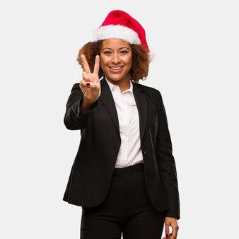 Jeune femme noire portant un bonnet de noel chirstmas montrant le numéro deux