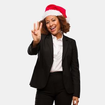 Jeune femme noire portant un bonnet de noel chirstmas montrant le numéro trois
