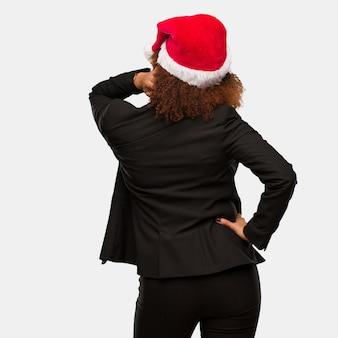 Jeune femme noire portant un bonnet de noel chirstmas par derrière, pensant à quelque chose