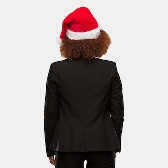 Jeune femme noire portant un bonnet de noel chirstmas par derrière, regardant en arrière