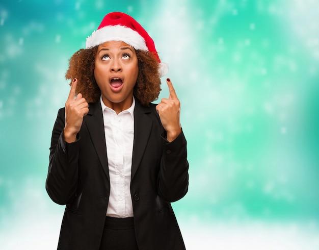 Jeune femme noire portant un bonnet de noël chirstmas surpris pointant vers le haut pour montrer quelque chose