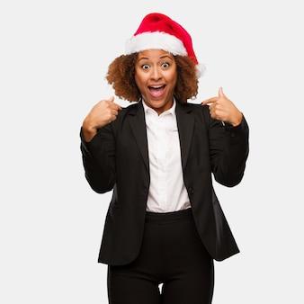 Jeune femme noire portant un bonnet de noël chirstmas surpris, se sent prospère et prospère