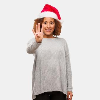 Jeune femme noire portant un bonnet de noel montrant le numéro quatre