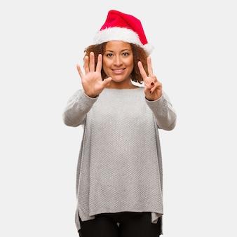 Jeune femme noire portant un bonnet de noel montrant le numéro sept