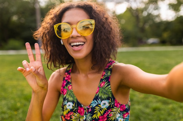 Jeune femme noire positive élégante prenant selfie photo en écoutant de la musique sur des écouteurs sans fil s'amuser dans le parc, style de mode estivale, tenue hipster colorée