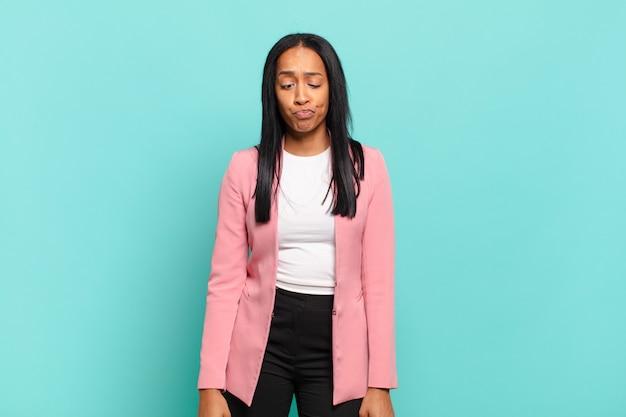 Jeune femme noire à la recherche maladroite et drôle avec une expression idiote aux yeux croisés, plaisantant et s'amusant. concept d'entreprise