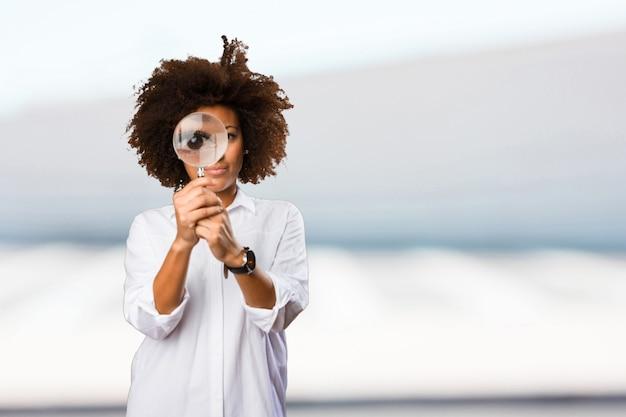 Jeune femme noire regardant à travers la loupe