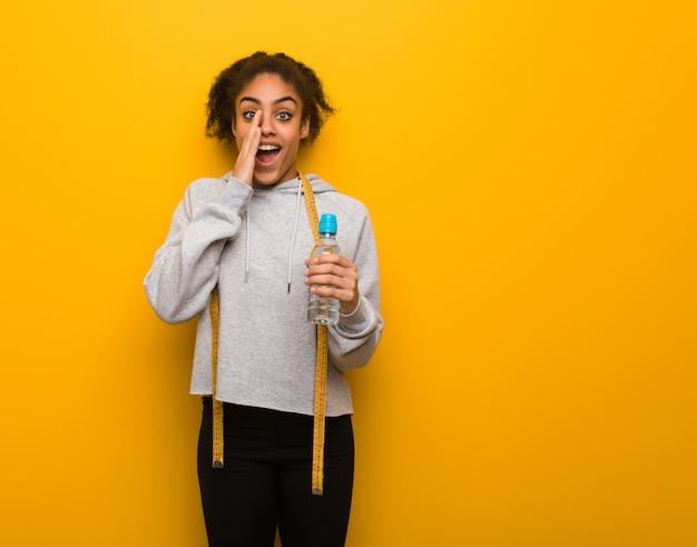 Jeune femme noire de remise en forme criant quelque chose de heureux à l'avant. tenant une bouteille d'eau.
