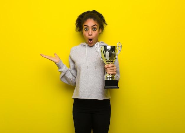 Jeune femme noire de remise en forme tenant quelque chose sur la main de la paume. tenant un trophée.