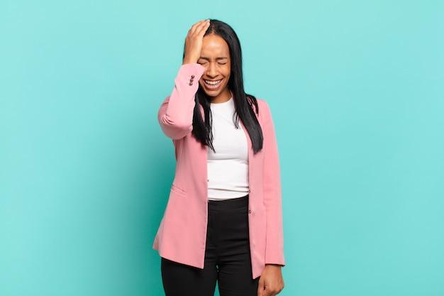 Jeune femme noire riant et giflant le front comme disant dãƒâ¢ã'â€ã'â™oh! j'ai oublié ou c'était une erreur stupide. concept d'entreprise
