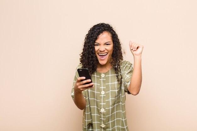 Jeune femme noire se sentant choquée, excitée et heureuse, riant et célébrant le succès, disant wow! avec un smartphone