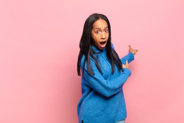 Jeune femme noire se sentant choquée et surprise, pointant vers l'espace de copie sur le côté avec un regard étonné et bouche bée