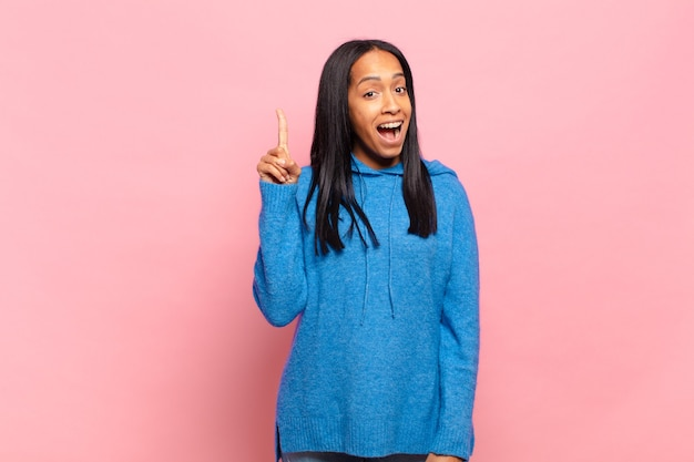 Jeune femme noire se sentant comme un génie heureux et excité après avoir réalisé une idée, levant joyeusement le doigt, eurêka!