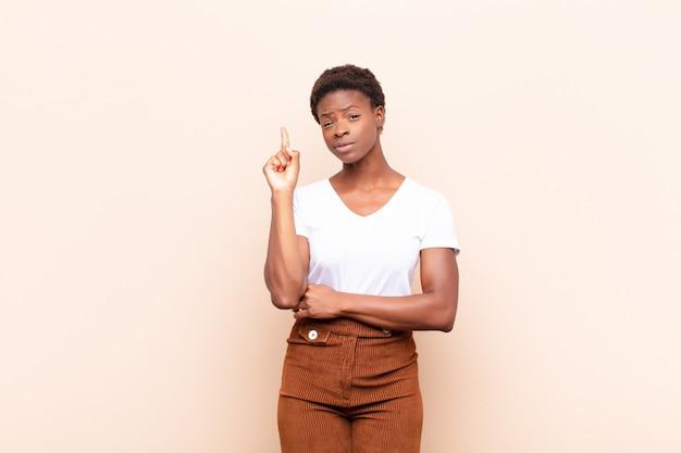Jeune femme noire se sentant comme un génie tenant fièrement le doigt en l'air après avoir réalisé une excellente idée, dit eureka