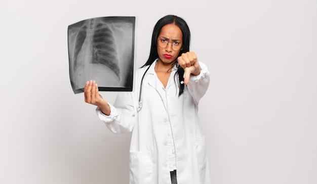 Jeune femme noire se sentant fâchée, en colère, agacée, déçue ou mécontente, montrant les pouces vers le bas avec un regard sérieux. médecin