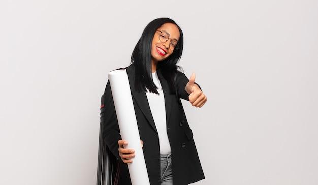 Jeune femme noire se sentant fière, insouciante, confiante et heureuse, souriant positivement avec les pouces vers le haut. concept d'architecte