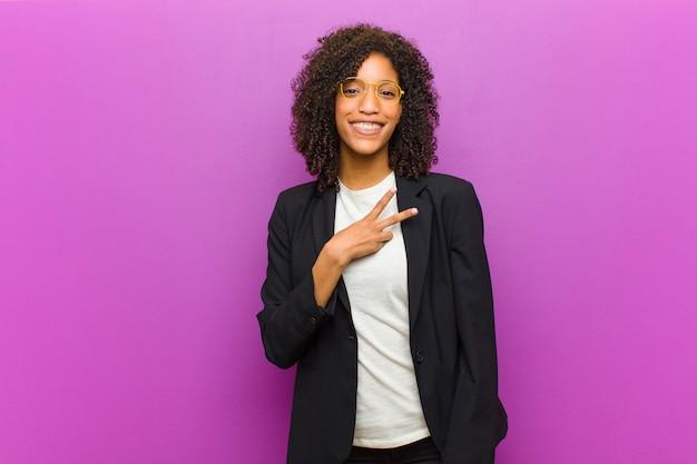 Jeune femme noire se sentant heureuse, positive et réussie, la main faisant la forme d'un v sur la poitrine, montrant la victoire ou la paix