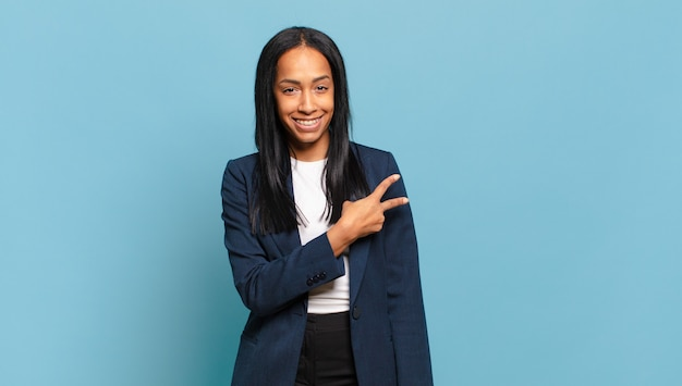 Jeune femme noire se sentant heureuse, positive et réussie, avec une main en forme de v sur la poitrine, montrant la victoire ou la paix. concept d'entreprise
