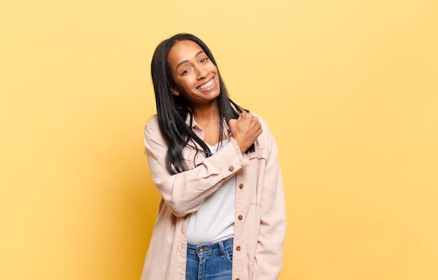 Jeune femme noire se sentant heureuse, positive et réussie, motivée face à un défi ou célébrant de bons résultats