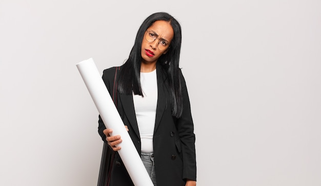 Jeune femme noire se sentant perplexe et confuse, avec une expression stupide et abasourdie en regardant quelque chose d'inattendu. concept d'architecte