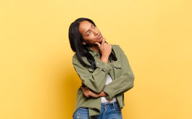 Jeune femme noire se sentant réfléchie, se demandant ou imaginant des idées, rêvant et levant les yeux pour copier l'espace