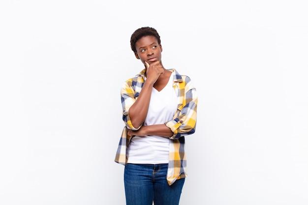 Jeune femme noire se sentant réfléchie, se demandant ou imaginant des idées, rêvassant et levant pour copier l'espace