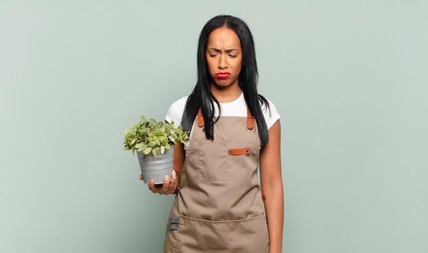 Jeune femme noire se sentant triste, bouleversée ou en colère et regardant sur le côté avec une attitude négative, fronçant les sourcils en désaccord. concept de jardinier
