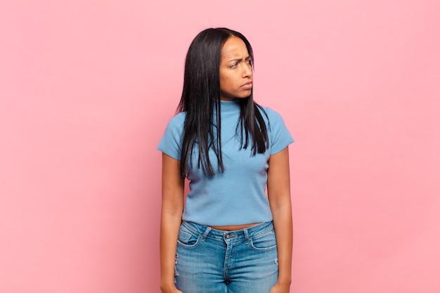 Jeune femme noire se sentant triste, bouleversée ou en colère et regardant de côté avec une attitude négative, fronçant les sourcils en désaccord