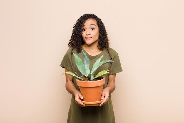 Jeune femme noire se sentir perplexe et confus, douter, pondérer ou choisir différentes options avec une expression drôle tenant un cactus