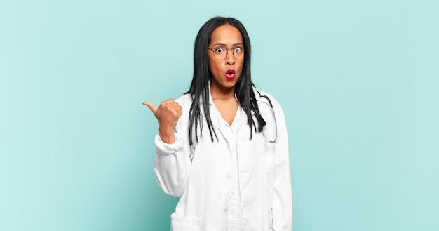 Jeune femme noire semblant étonnée d'incrédulité, pointant l'objet sur le côté et disant wow, incroyable. concept de médecin
