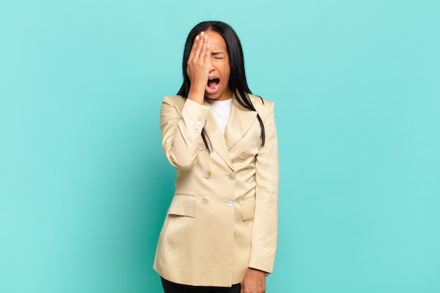 Jeune femme noire à la somnolence, s'ennuie et bâille, avec un mal de tête et une main couvrant la moitié du visage. concept d'entreprise