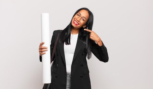 Jeune femme noire souriant avec confiance en montrant son large sourire, attitude positive, détendue et satisfaite. concept d'architecte
