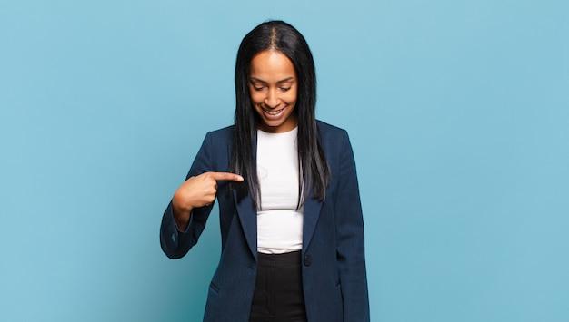 Jeune femme noire souriant gaiement et avec désinvolture, regardant vers le bas et pointant vers la poitrine.