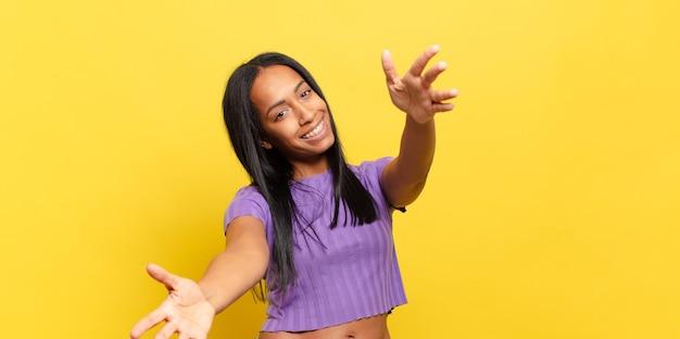 Jeune femme noire souriant joyeusement donnant un câlin de bienvenue chaleureux, amical et affectueux, se sentant heureuse et adorable