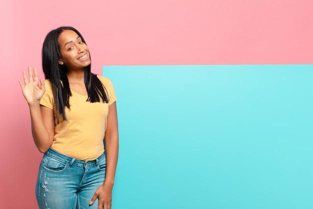 Jeune femme noire souriant joyeusement et gaiement, en agitant la main, en vous accueillant et en vous saluant, ou en vous disant au revoir. copie concept d & # 39; espace