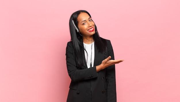 Jeune femme noire souriant joyeusement, se sentant heureuse et montrant un concept dans l'espace de copie avec la paume de la main. concept de télémarketing
