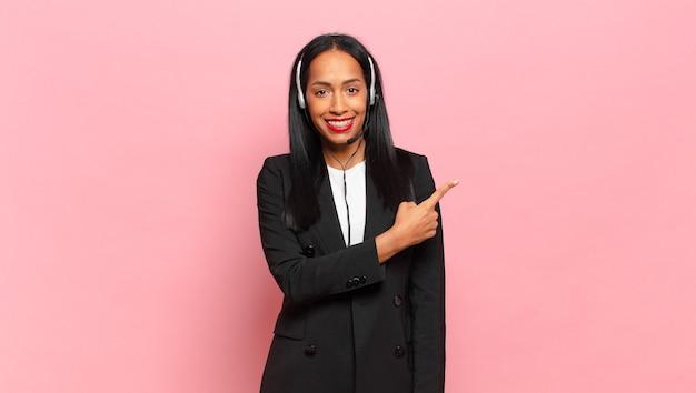 Jeune femme noire souriant joyeusement, se sentant heureuse et pointant vers le côté et vers le haut, montrant l'objet dans l'espace de copie. concept de télémarketing