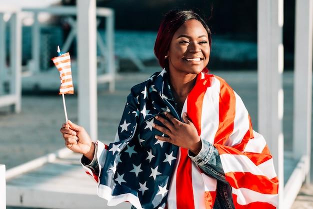 Jeune femme noire souriante avec des drapeaux des états-unis