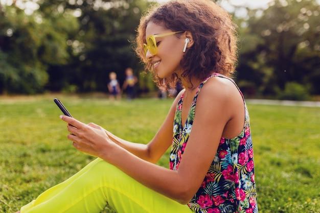 Jeune femme noire souriante élégante à l'aide de smartphone, écouter de la musique sur des écouteurs sans fil s'amuser dans le parc, style coloré de la mode estivale