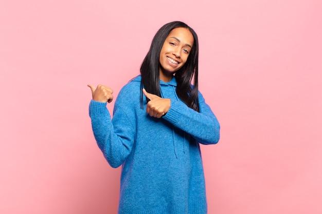 Jeune femme noire souriante gaiement et désinvolte pointant vers l'espace de copie sur le côté, se sentant heureuse et satisfaite