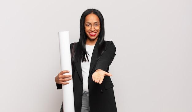 Jeune femme noire souriante joyeusement avec un regard amical, confiant et positif, offrant et montrant un objet ou un concept. concept d'architecte