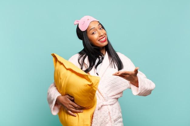Jeune femme noire souriante joyeusement, se sentant heureuse et montrant un concept dans l'espace de copie avec la paume de la main. concept de pyjama